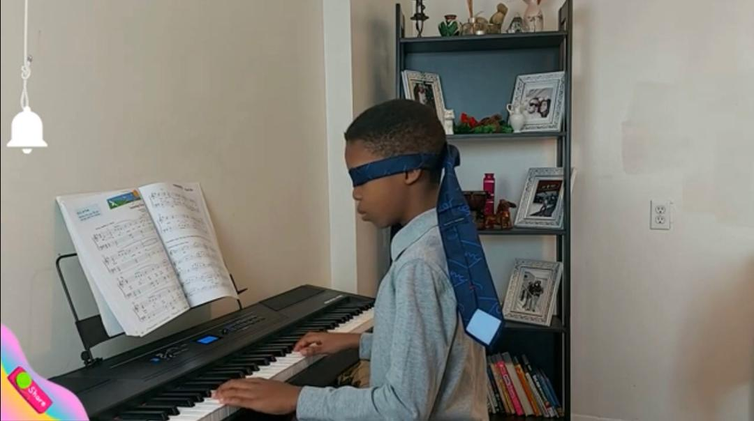 "The video shows the young boy playing the popular song ""Amazing Grace"" with his eyes covered."